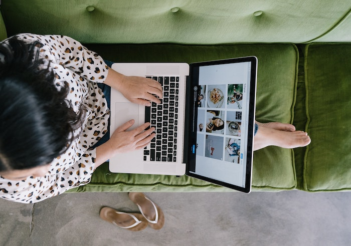 Girl sitting on an olive green sofa with her feet up and laptop on het lap.